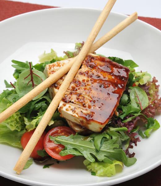 Tofu in Gewürzglasur auf buntem Salat und Grissini